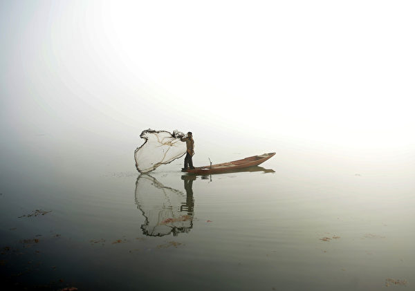 2016年1月13日,斯利那加达尔湖,一名克什米尔渔民从船上抛出了渔网,当时的浓雾使图片如置身于山水画中。(Tauseef MUSTAFA/ AFP)