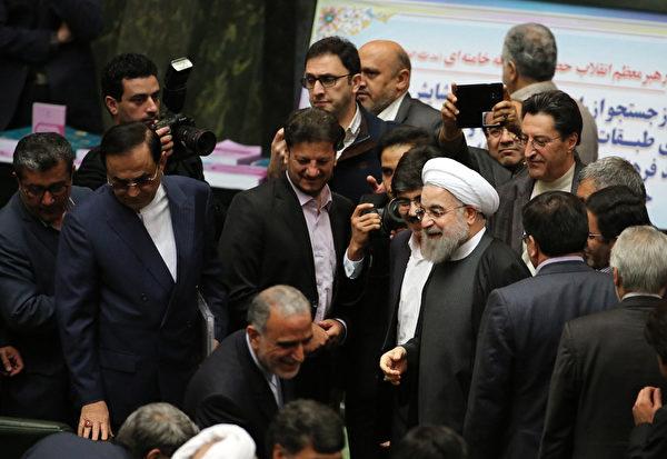 """2016年1月17日,在国际原子能总署确认伊朗已履行与""""五常加一""""达成的核子协议后,美国及欧盟国家16日解除对伊朗的经济与金融制裁,伊朗总统罗哈尼表示,伊朗与世界的关系""""已经开启了新篇章""""。图为鲁哈尼(中着白头巾者)17日抵达国会,准备提交政府的年度预算案。(ATTA KENARE/AFP)"""