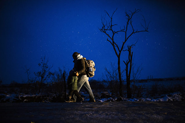2016年1月17日,穿越马其顿-塞尔维亚边界后,一名男性和他的孩子步行穿过黑夜的Miratovac村附近的雪地。根据联合国难民署统计,有超过百万的非法移民在2015年到达欧洲,其中大部分难民是企图逃离阿富汗、伊拉克和叙利亚的战争与暴力。(DIMITAR DILKOFF/AFP)
