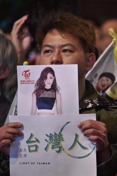 2016年1月16日,台湾的民主进步党(民进党)的支持者举着韩国JYP公司女团TWICE台湾成员周子瑜的相片表示支持,周子瑜因持中华民国国旗遭中国抵制被强迫道歉的事件,迅速变成台湾焦点,并影响了众多年轻人参与台湾大选投票的意愿及开票结果。(Philippe Lopez/AFP)