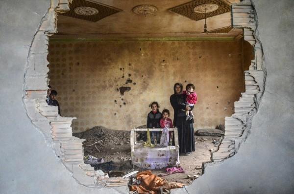 2016年1月19日,土耳其东南,伊拉克边境附近锡洛皮的库尔德城镇,一名妇女和她的孩子站在战斗中损坏的房屋废墟中。近日土耳其发动对库尔德工人党(PKK)的全面进攻,双方武装冲突不断。(ILYAS AKENGIN/AFP)