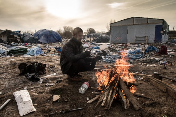 """2016年1月18日,法国北部港口加来,一位库尔德人移民,在被称为""""丛林""""的临时营地火堆旁取暖。当地警局警示他们,几天内将要清除马路边上窝棚中以木板和帆布搭成的帐篷区。目前约有两千多名难民聚集于此,企图由加来闯进英国。(PHILIPPE HUGUEN/AFP)"""