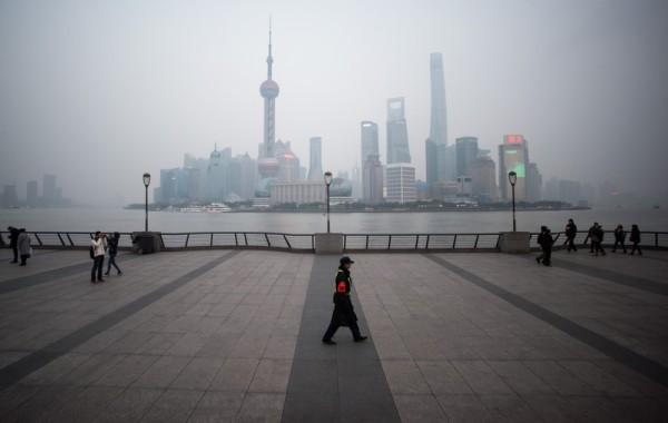 2016年1月18日,中国上海,上海经济增长面临放缓,据法新社的调查预测,中国这个世界第二大经济体今年的增长将进一步放缓。图为一名保安走在横跨浦东新区金融区的黄浦江外滩。(JOHANNES EISELE/AFP)