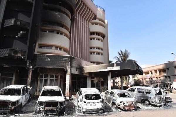 2016年1月16号,伊斯兰北非盖达组织(AQIM)坦承在布吉纳法索首都瓦加杜古外国访客喜爱的辉煌酒店(左)和旁边的卡布奇诺餐厅(右)进行袭击和人质挟持,至少有26人被杀害。后军警部队包围酒店攻坚击毙恐怖份子。图为酒店前方的一片狼藉和被烧毁的车辆。(ISSOUF SANOGO/AFP/Getty Images)