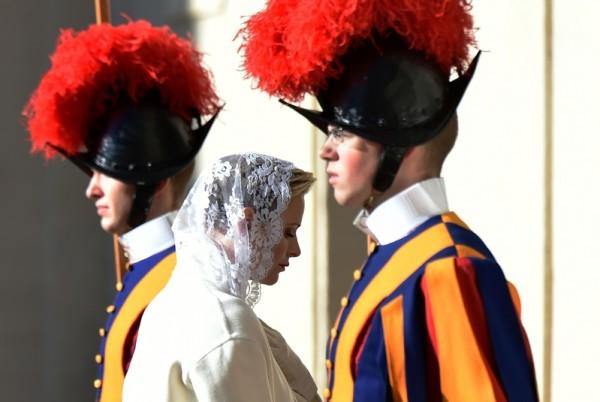 2016年1月18日,梵蒂冈,摩纳哥夏琳王妃(中)穿了一身白衣和亚伯特国王访问教廷,在方济各教宗卫队旁通过。依照梵蒂冈的规矩,只有七名天主教国家的女王或王妃可以穿白衣服见教宗。(ALBERTO PIZZOLI/AFP/Getty Images)