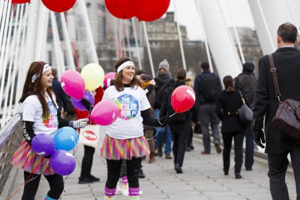 """2016年1月18日,英国伦敦,号称全地球最快乐的五公里路跑Color Run在伦敦市中心举办,工作人员将五彩缤纷的气球送给通勤者,愿大家能笑对假期后的""""蓝色星期一""""。(Tristan Fewings/Getty Images for The Color Run)"""