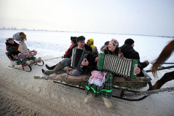 2016年1月21日,白俄罗斯明斯克东部Martsiyanauka,一位男性和一位女性乘坐着马拉的雪橇,沿路歌唱和弹奏手风琴庆祝冬季的Kolyada holiday。(SERGEI GAPON/AFP)