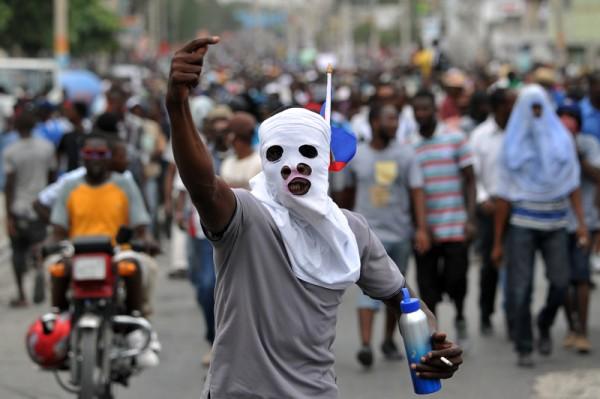 2016年1月22日,海地选委会宣布因选前暴力频传,再度延后原本即将在24日举行的总统大选。许多认为选举充满舞弊而上街头示威的民众欢声雷动,但是镇暴警察随即与示威民众发生暴力冲突,甚至开枪镇压示威群众。(HECTOR RETAMAL/ AFP)