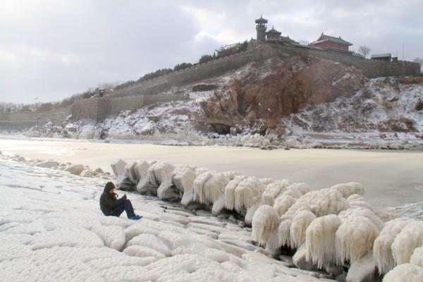 2016年1月24日,中国东山东省蓬莱市海边,海边的岩石已和海水一起结冻。强寒潮持续袭击中国大陆各地,本次寒潮上海遭遇36年来最冷早晨;广州1949年后首次下雪;浙江出现-20℃最低温,重庆时隔20年再下雪。(AFP)