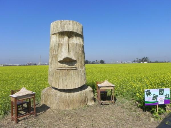 嘉新國中在黃澄澄的油菜花海中,以稻草為主題,做成的小巨人造型裝置藝術很壯觀。(蔡上海/大紀元)
