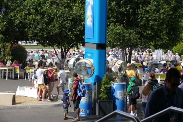 網球村內設置的濕霧噴射扇前站著許多為消暑吹濕霧的人。(燕楠/大紀元)