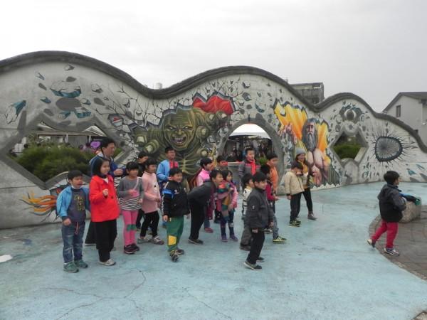 大小朋友來到「好美漁村公園」參觀全台最大3D彩繪地畫-《抹香鯨大戰大王烏賊》,在驚奇之餘,擺出各種姿勢拍照,好玩又有趣。(蔡上海/大紀元)