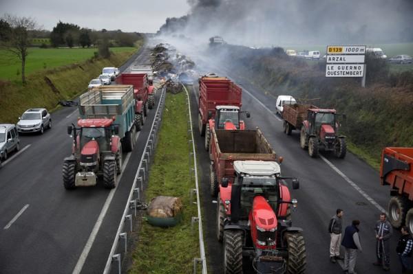 2016年1月29日,法国雷恩市的市政府召开农业问题圆桌会议的前一天。法国各地的农民堵截了十多条交通要道,几个地点进行示威游行,抗议蛋奶等农产品价格过低让农民支撑不下去。图为高速公路RN165上农民设立的路障。(DAMIEN MEYER/ AFP)