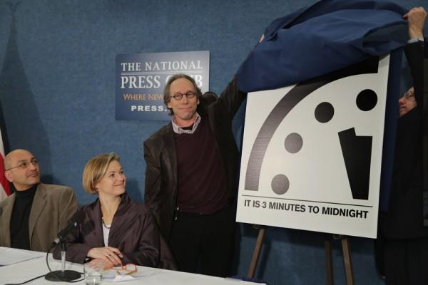 """2016年1月26日,美国华盛顿特区,美国亚利桑那州立大学的新起源计划主管劳伦斯.克劳斯(中)和原子科学家科学与安全委员会成员托马斯.皮克林(右站立者)向媒体发表""""末日之钟""""指针的动向──距离午夜三分钟。此公告考虑到""""世界核武器数量、大气中的二氧化碳、海洋酸度和海平面上升的速度""""作为对地球人的警告。(Chip Somodevilla/Getty Images)"""