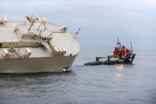 """2016年2月2日拍摄,西班牙拖轮""""半人马座""""(右)尝试牵引巴拿马籍货轮""""现代快报""""。该货船在西班牙海岸外150英哩处遭遇强风大浪,整艘货船倾斜。22名水手已被救出,载运的3,600吨重的木材与营造设备,目前已漂到法国海域。 (MARINE NATIONALE/AFP)"""