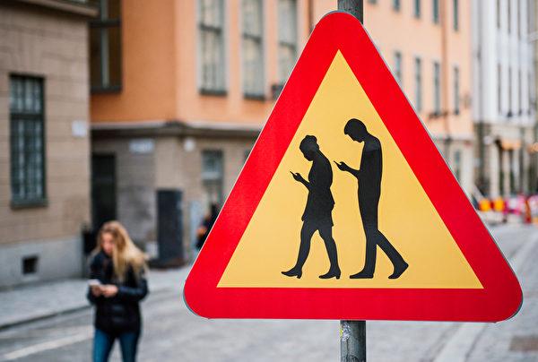 2016年2月2日,在斯德哥尔摩附近的老城区,出现针对专注于智能手机的低头族行人的警告交通标志,令人莞尔。(JONATHAN NACKSTRAND/AFP)
