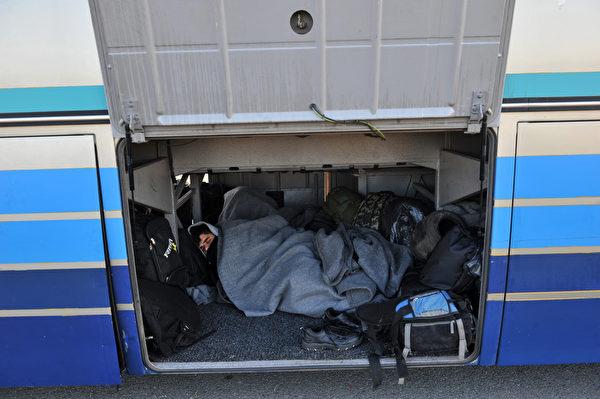 2016年2月3日,希腊北部村庄Idomeni附近,一个难民睡在的一辆停放在加油站公交车的行李舱中,他们期望穿越希腊和马其顿边界。难民也为马其顿的出租车司机们带来了额外收入,由于对难民们收取高价费用,当局对出租车行业进行了干预,从而引发出租车司机与警方之间的冲突。(SAKIS MITROLIDIS/AFP)