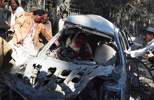 2016年2月6日,巴基斯坦西南部城市奎达市中心发生针对安全部队车队的炸弹袭击,造成至少8人死亡,35人受伤。至少3辆车被炸毁。图为巴基斯坦居民试图帮助一名在炸弹爆炸中受伤的男子。(BANARAS KHAN/AFP)