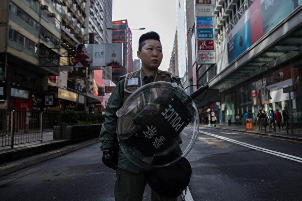 2016年2月9日凌晨,香港旺角街头爆发97后最严重的警民冲突。有本土派团体原本集会支持小贩摆档,其后与警方多次冲突,警员期间两度向天鸣枪示警并施放催泪瓦斯,大批示威者则向警方投掷垃圾桶、玻璃樽、砖块等杂物,并在街头多处纵火。图为一位香港女警站在封锁区警戒。(DALE DE LA REY/AFP)