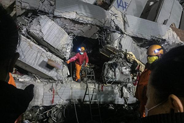 2016年2月9日,台湾6日凌晨3时57分发生规模6.4强震,台南维冠金龙大楼倒塌,强震共造成116人罹难,其中维冠大楼罹难人数114人。图为搜救人员把握黄金72小时深入倒塌的大楼通道中搜寻生还者。(ANTHONY WALLACE/AFP)