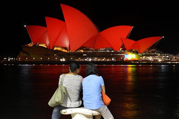 2016年2月8日,澳洲悉尼,中国游客并肩坐下观看悉尼歌剧院在黄历新年以红色灯光点缀,迎接猴年新年于2月8日开始。(Peter PARKS/AFP)
