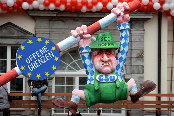 這位穿著巴伐利亞服裝的卡通人物努力把邊境的欄杆拉下來,他就是基社盟主席、巴伐利亞州長西霍夫,他的名字寫在帽子上,身上的牌子寫著基社盟。該黨一直主張接收難民的數量要限制,一年最多20萬,但默克爾不同意。(Sascha Steinbach/Getty Images)