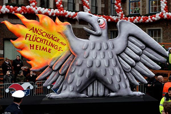 這隻老鷹的翅膀被燒紅了,老鷹代表德國,翅膀上的字寫著:襲擊難民營。(PATRIK STOLLARZ/AFP/Getty Images)