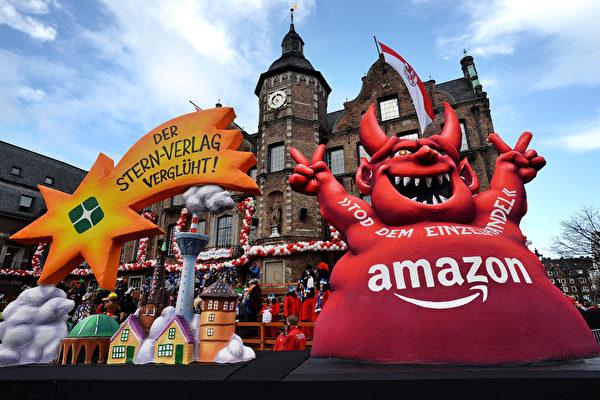 這個魔鬼一樣的亞馬遜越來越肥,它吃死了零售商,邪惡地比著勝利的剪刀手。(PATRIK STOLLARZ/AFP/Getty Images)
