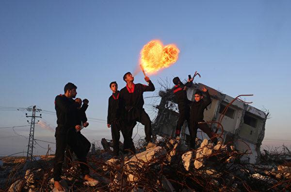 2016年2月11日,加沙地带北部拜特哈嫩,一个巴勒斯坦青年,加沙武术组的成员在一个2014年被摧毁的房屋废墟上表演喷火,火焰在他的吸吐中意外形成了心型。(MOHAMMED ABED/AFP)