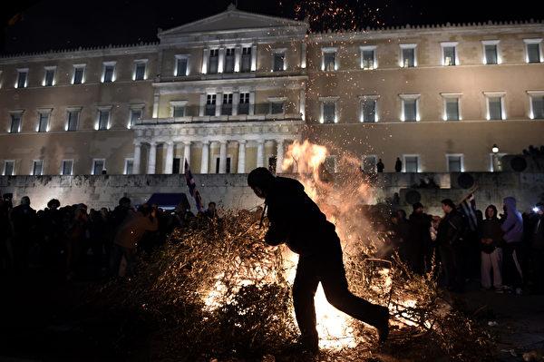 """2016年2月12日,希腊雅典,近千名克里特农民反对养老金改革的集会,农民和警方发生冲突,砖块和棍棒齐飞。国际市场也担心如果希腊当局没有拿出""""可信任""""的改革方案,希腊将退出欧元区。图为农民在希腊议会前放火。(ARIS MESSINIS/AFP)"""