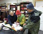 文海倫(戴紅帽者)13日手上拿著厚厚一疊已簽名的請願書給趙文笙。(蔡溶/大紀元)