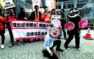 請願人士將訴求寫在桃形狀紙牌上,象徵香港市民要做靈猴,在財政司司長手上「偷桃」。他們反對政府削減部門開支,要求繼續加大醫療方面的經常開支。(蔡雯文/大紀元)