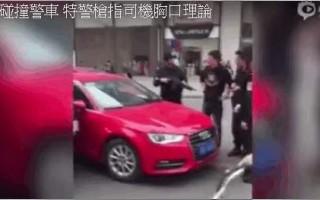 近日,一个视频在网络被热传,四川成都一名男子驾驶一辆红色奥迪(Audi)私家车,在并线时不慎碰到一辆特警装甲车。车上数名特警下车与男子理论,其中一特警荷枪实弹、全副武装,更一度用枪指向私家车司机胸口。网民热议指,特警滥用枪支,行为过激。(视频截图)