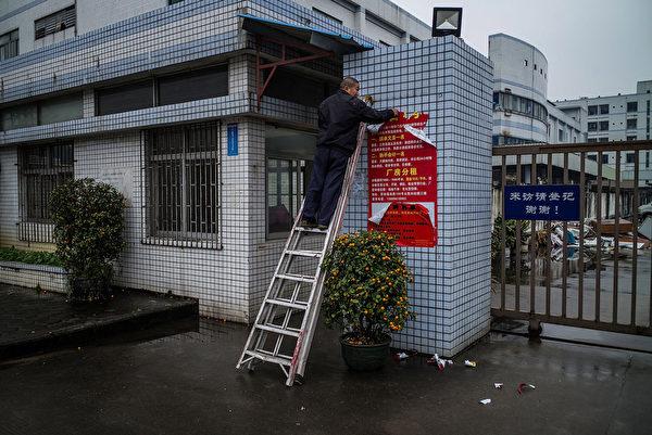 大陆经济寒冬持续,在制造业中心东莞,去年就有近4万家企业倒闭。图为,2016年1月27日,东莞一家倒闭的工厂门口,一名男子正撕下分租广告。 (Lam Yik Fei/Getty Images)