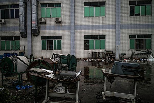 大陆经济寒冬持续,在制造业中心东莞,去年就有近4万家企业倒闭。图为,2016年1月26日,东莞一家倒闭的工厂的设备被遗弃在外面。 (Lam Yik Fei/Getty Images)