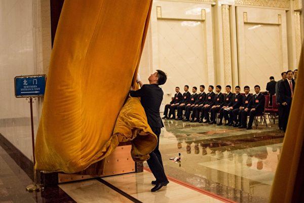 """每年中共""""两会""""安保都异常紧张,如临大敌,会场内总有一批神秘的""""黑衣人""""无时无刻地在监视着一切。图为,2016年3月5日,人民大会堂内的统一穿黑西装的保安人员。(FRED DUFOUR/AFP/Getty Images)"""