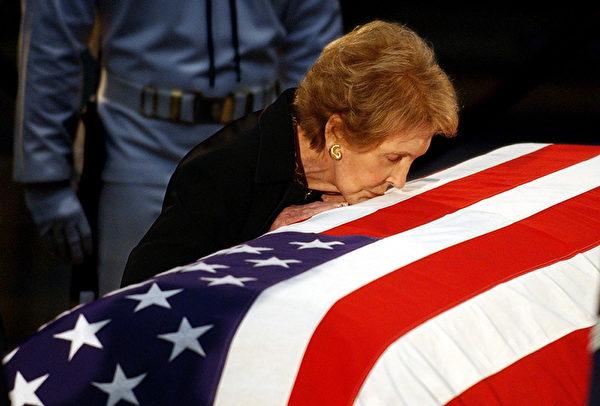南希‧里根2004年亲吻覆盖国旗的里根灵柩。(AFP / ROBERTO SCHMIDT)