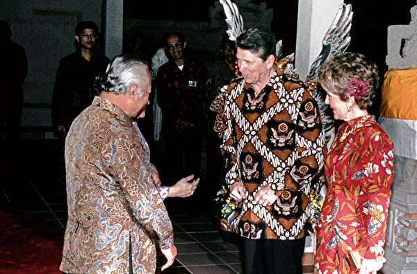 1986年5月1日,当时的美国总统里根穿着蜡染衬衫,和印尼当时的总统苏哈托谈话,第一夫人南希在里根身边。(AFP)