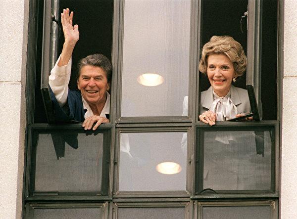 1987年1月6日,当时的美国总统里根和第一夫人南希在贝塞斯达海军医院(Bethesda Naval Hospital)的房间窗口向新闻界挥手。(AFP / MIKE SARGENT)