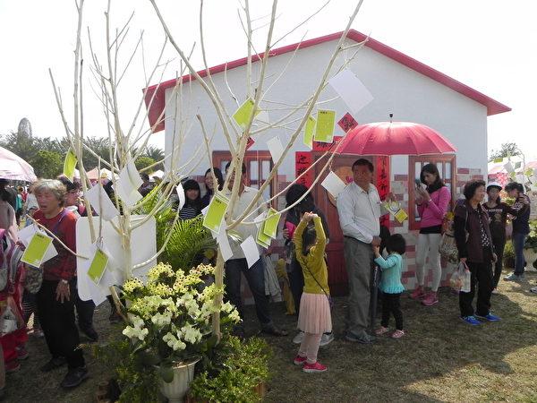 嘉義縣105年度婦女節「38女生同樂會」慶祝活動現場,許多婦女朋友在幸福小屋前的祈願樹上掛上祈願卡,並在牆壁貼上許多築夢卡與傳愛卡。(蔡上海/大紀元)