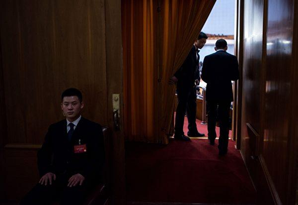 """每年中共""""两会""""安保都异常紧张,如临大敌,会场内总有一批神秘的""""黑衣人""""无时无刻地在监视着一切。图为,2016年3月5日,人民大会堂内的统一穿黑西装的保安人员。(JOHANNES EISELE/AFP/Getty Images)"""