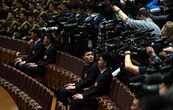 """每年中共""""两会""""安保都异常紧张,如临大敌,会场内总有一批神秘的""""黑衣人""""无时无刻地在监视着一切。图为,2016年3月7日,人民大会堂内的统一穿黑西装的保安人员坐在记者前。(JOHANNES EISELE/AFP/Getty Images)"""