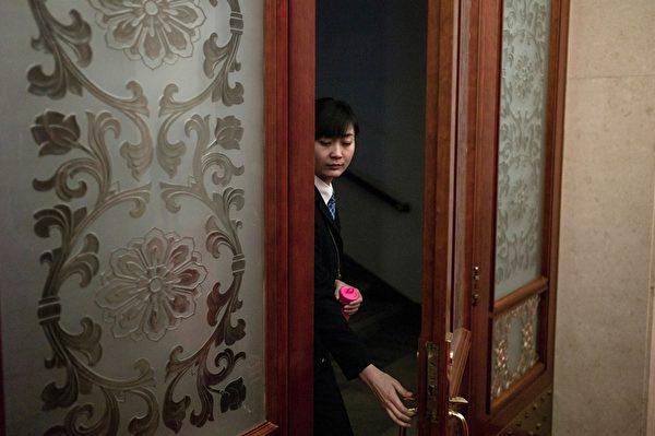 """每年中共""""两会""""安保都异常紧张,如临大敌,会场内总有一批神秘的""""黑衣人""""无时无刻地在监视着一切。图为,2016年3月8日,人民大会堂内的统一穿黑西装的保安人员。(FRED DUFOUR/AFP/Getty Images)"""