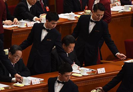 2016年3月5日,中共兩會上男服務生在給習近平和中共政治委員倒水。(GREG BAKER/AFP/Getty Images)
