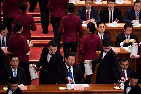 2016年3月3日,中共兩會上男服務生在給中共政治委員倒水。(JOHANNES EISELE/AFP/Getty Images)