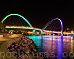 西澳首府珀斯夜色中的伊麗莎白碼頭大橋。這座110米長的人行大橋橫跨碼頭水灣相連天鵝河的入口水面,橋面5米寬,有自行車道和行人跑道。整個大橋呈S形狀,在弧度最大的兩處橋段,各向半空中伸起弓形的巨大鋼臂,用鋼絲把下面對應的橋面吊住。(周鑫/大紀元)
