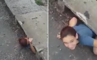聽到街頭下水道中傳來一隻小貓咪求救的叫聲,這位女士鑽入了下水道。(視頻截圖/大紀元合成)