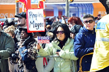 圣詹姆斯大教堂前挤满前来悼念福特的市民,一名亚裔女性举着People's Mayor(人民的市长)的牌子,向福特的灵柩致意。(周行/大纪元)