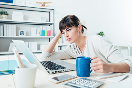 累了困了女人在办公桌工作,拿着咖啡,过度劳累和睡眠剥夺概念一杯(fotolia)