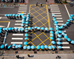 台灣勞工陣線29日號召近200名群眾到立法院前排字,撐起藍色雨傘共同排出「26K」字樣,呼喊「反血汗、要公平」,要求政府「提高基本工資至26K」。(陳柏州/大紀元)